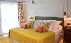 Colores vivos y elegancia en la reforma de esta habitación doble tipo suite con baño