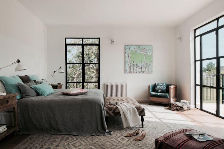 Dormitorio principal: mesillas de Bloomingville, arte contemporáneo, butaca tapizada con denim, de Labyrinthe Interiores, y almohadón de suelo con tela marroquí, de Arne Jacobsen.