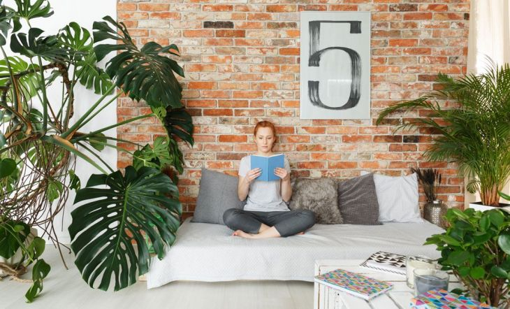 mujer leyendo cama hojas